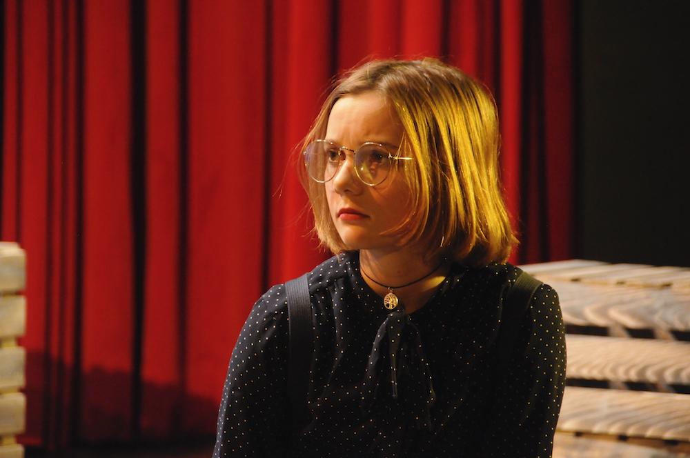 Blondes Mädchen mit Brille, im Hintergrund Theatervorhang