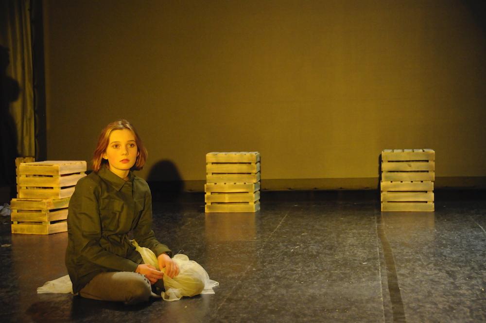 Mädchen sitzt verloren auf einer Bühne, blickt ins Leere